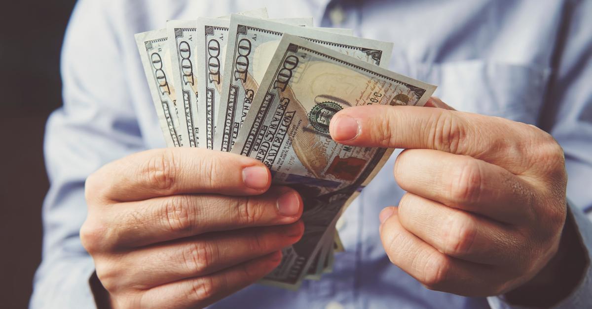 hands counting money, dollar bills